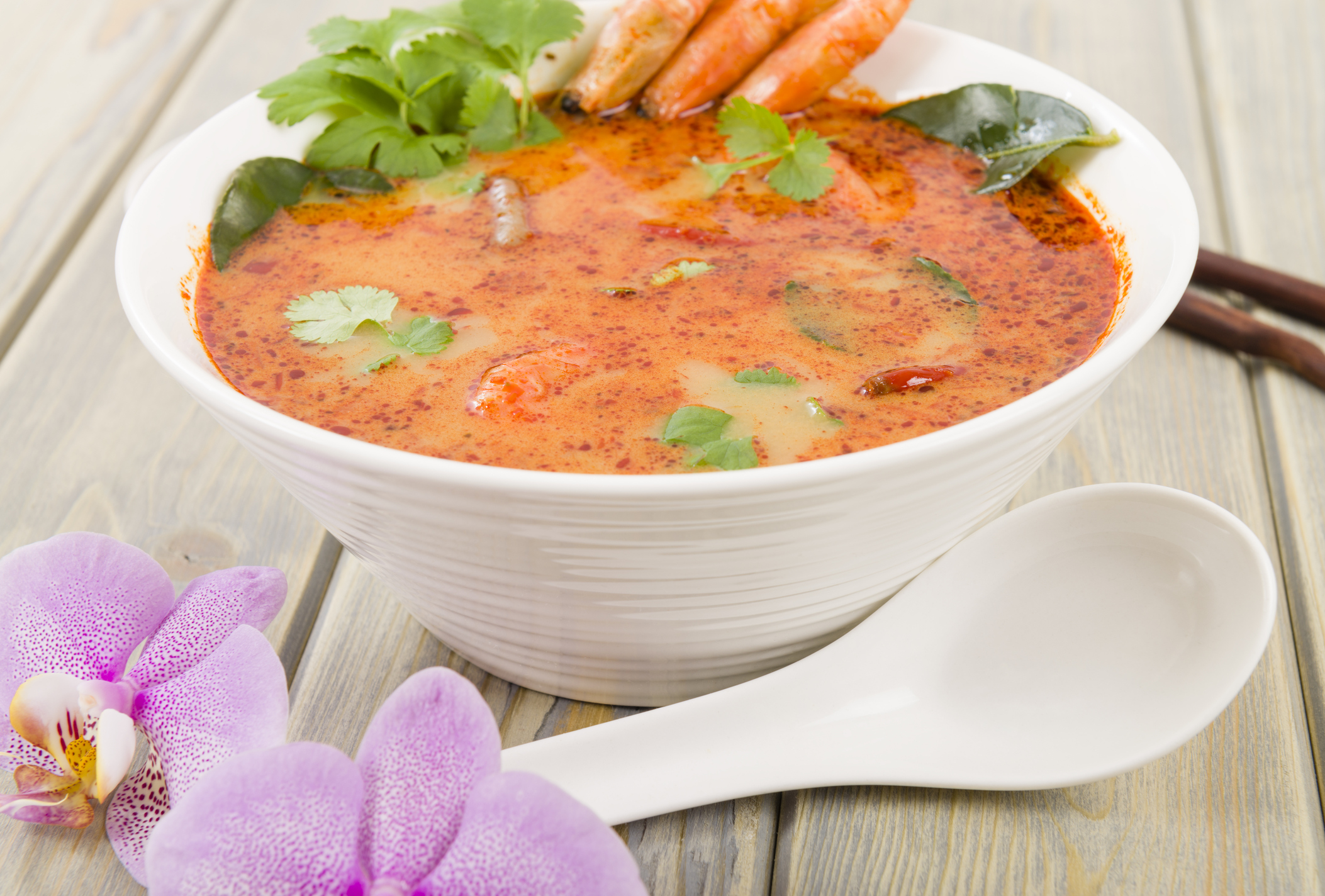 Creamy Thai soup with prawns and mushrooms garnished with coriander leaves and served with lime wedges.